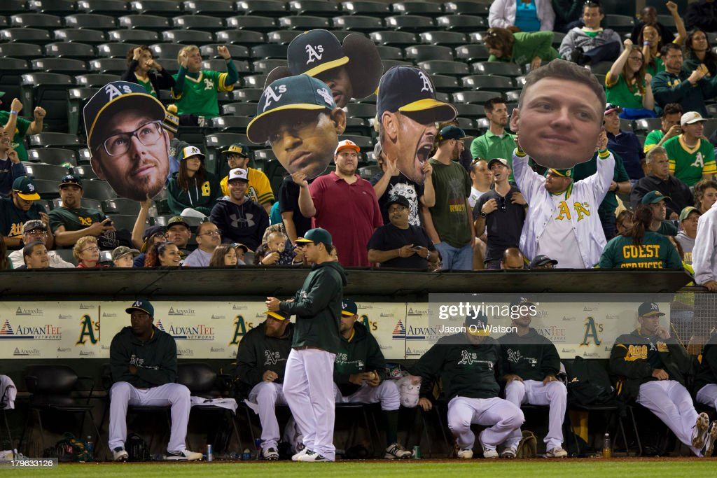 Oakland Athletics fans hold up cut outs of players in the stands during the eighth inning against the Houston Astros at O.co Coliseum on September 5, 2013 in Oakland, California.