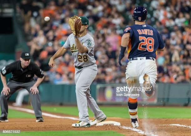 Oakland Athletics first baseman Matt Olson makes an out on Houston Astros third baseman JD Davis during the MLB game between the Oakland Athletics...
