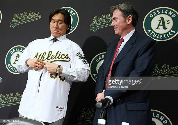 Oakland Athletics general manager Billy Beane looks on as Hideki Matsui buttons his new jersey during a press conference where he was introduced as...