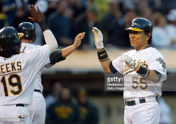 Oakland Athletics' Hideki Matsui, right, smiles as he is congratulated at home by teammates Jemile Weeks and Landon Powell on his three-run homer off...