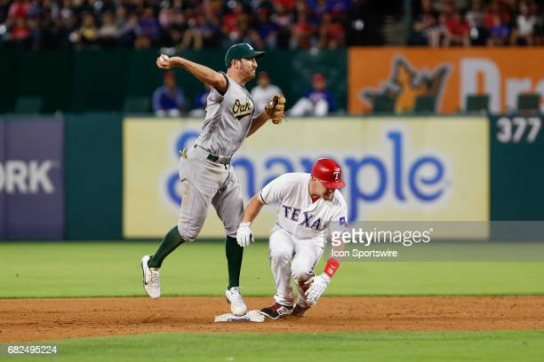 Oakland Athletics Infield Adam Rosales turns a double play with Texas Rangers Outfield Ryan Rua sliding into second during the MLB game between the...