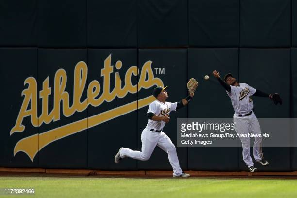 Oakland Athletics' Jake Smolinski and Danny Valencia retrieve the ball on a double hit by Cleveland Indians' #13Brandon Guyer in the fifth inning of...