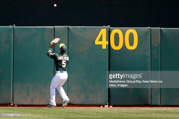 Oakland Athletics' Jake Smolinski waits for the ball to bounce back off the wall on a double hit by Seattle Mariners' Nelson Cruz in the first inning...