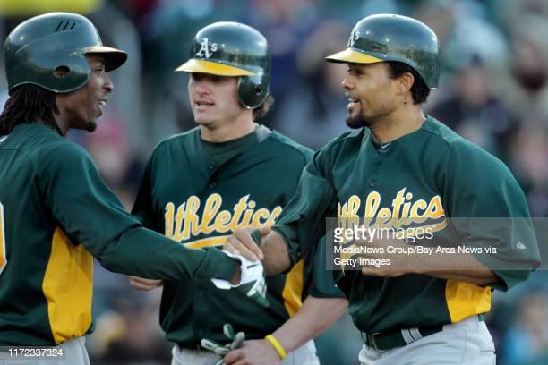 Oakland Athletics' Jemile Weeks and Josh Donaldson celebrate Coco Crisp three-run homerun off Sacramento River Cats pitcher Jarrod Parker in the...