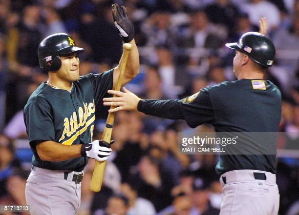 Oakland Athletics Johnny Damon gets a highfive from the ball boy after scoring off a single by Miguel Tejada in the ninth inning during their game...