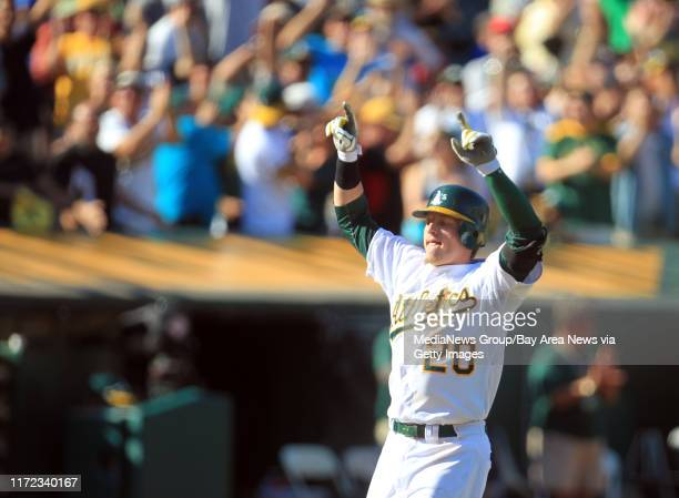 Oakland Athletics' Josh Donaldson raises his arms in celebration as he ties the game with his tworun homer against the Seattle Mariners in the ninth...