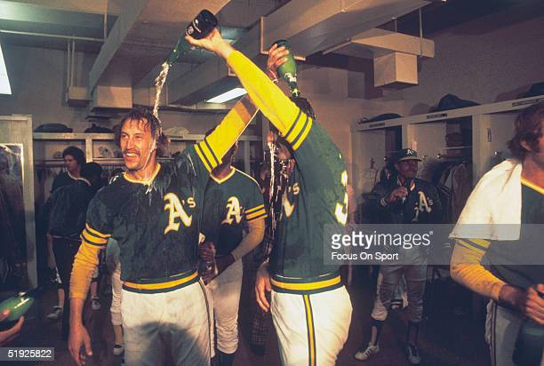Oakland Athletics' Ken Holtzman and Rollie Fingers celebrate in the clubhouse after defeating the Baltimore Orioles to win the American League...