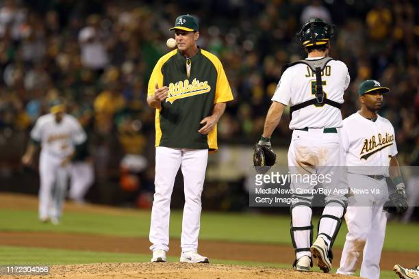 Oakland Athletics manager Bob Melvin flips the ball after replacing starting pitcher Tommy Milone for Dan Otero against Texas Rangers in the sixth...