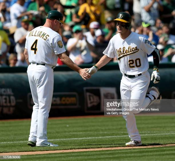 Oakland Athletics' Mark Canha is congratulated by third base coach Matt Williams after hitting a solo home run off New York Yankees starting pitcher...