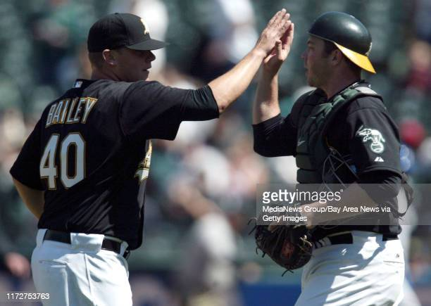 Oakland Athletics' pitcher Andrew Bailey high fives catcher Landon Powell after beating the Texas Rangers with a final score of 4-1 at the...