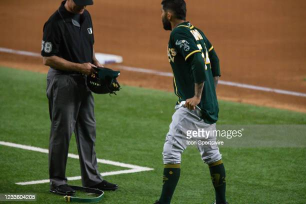 Oakland Athletics Pitcher Sergio Romo gives third base umpire Dan Iassogna his hat, glove, and belt to check and pulls down his pants during the...