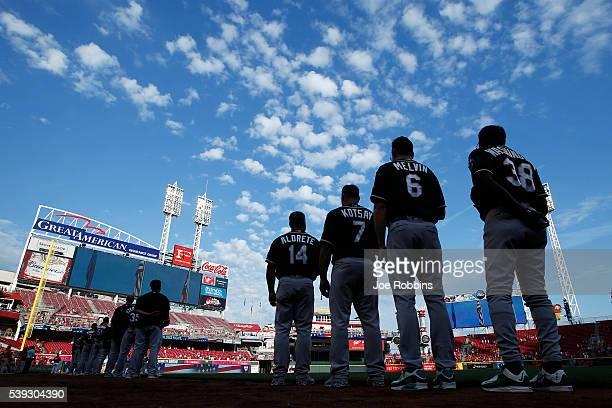 Oakland Athletics players and coaches stand during the national anthem prior to the game against the Cincinnati Reds at Great American Ball Park on...