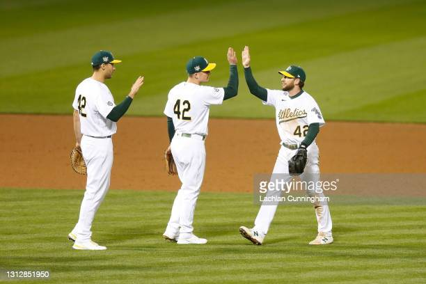 Oakland Athletics players Matt Olson, Matt Chapman and Jed Lowrie celebrate after a win against the Detroit Tigers at RingCentral Coliseum on April...