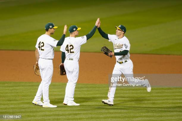 Oakland Athletics players Matt Olson, Matt Chapman and Mark Canha celebrate after a win against the Detroit Tigers at RingCentral Coliseum on April...
