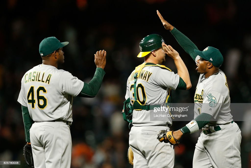 Oakland Athletics players Santiago Casilla #46, Ryan Lavarnway #30 and Rajai Davis #11 celebrate a win in an interleague game against the San Francisco Giants at AT&T Park on August 2, 2017 in San Francisco, California.