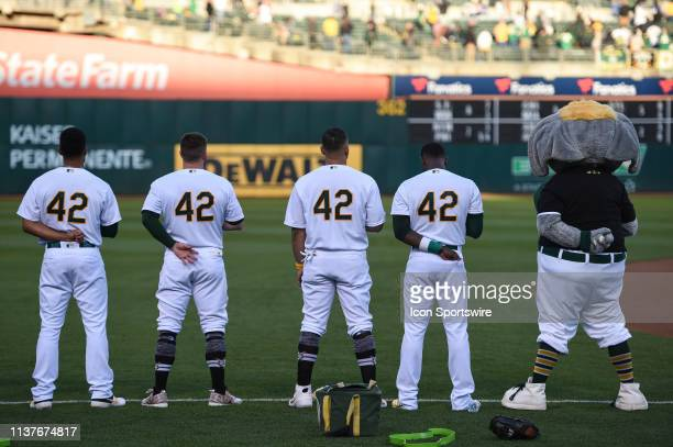 Oakland Athletics players wearing number 42 and their mascot Stomper stand for the national anthem on Jackie Robinson Day prior to the Major League...