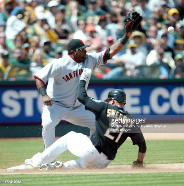 Oakland Athletics' Ryan Sweeney slldes safe at third base as San Francisco Giants' Pablo Sandoval awaits the throw in the sixth inning of their MLB...