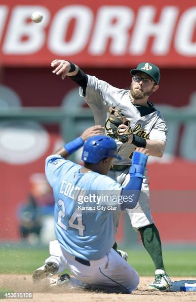 Oakland Athletics shortstop Eric Sogard turns a double play over the Kansas City Royals' Christian Colon at second base to end the fifth inning on...