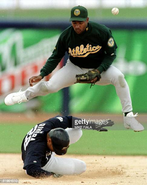 Oakland Athletics' shortstop Miguel Tejada forces out San Diego Padres' Ruben Rivera at second base but is unable to throw out Padres' Tony Gwynn at...