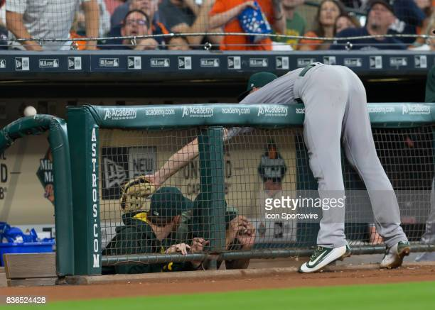 Oakland Athletics third baseman Matt Chapman reaches but fails to catch a ball that fell in the visitors' dugout during the MLB game between the...