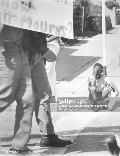 Oakland CA 8 April 1968 A young boy wipes away tears as a Black Panther Party and Peace and Freedom sponsored march heads east on 49th StreetSign at...