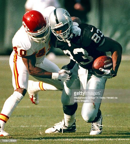 Raiders tight end Rickey Dudley tries to break away from Kansas City defender James Hasty