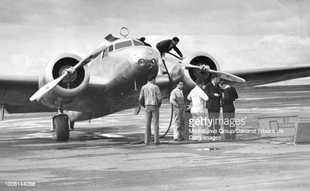 Oakland, CA March 19, 1937 - George Palmer Putnam works with mechanics on Amelia Earhart's plane at the Oakland Airport.