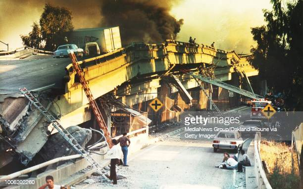 Oakland, CA October 17, 1989: Two people, lower right, comfort an injured motorist after he was pulled from the collapsed wreckage of the Cypress...