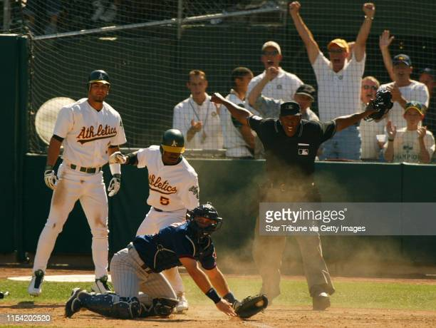 Oakland CA Twins vs Oakland Game two Home plate umpire Chuck Meriwether calls Ray Durham of Okland safe at home as Twins catcher AJ Pierzynski is...