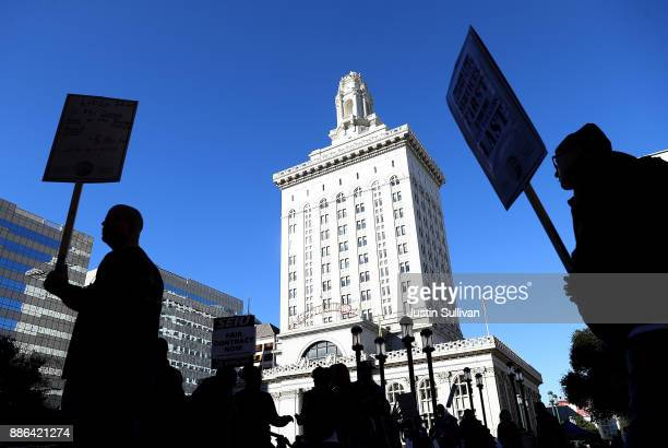 Oakland city workers carry signs as they picket outside of Oakland City Hall on December 5 2017 in Oakland California Thousands of Oakland city...