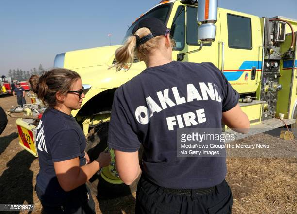 OCTOBER 29 Oakland firefighters Nicole McCall left and Alissa Larson do maintenance on their Office of Emergency Services firetruck after coming off...