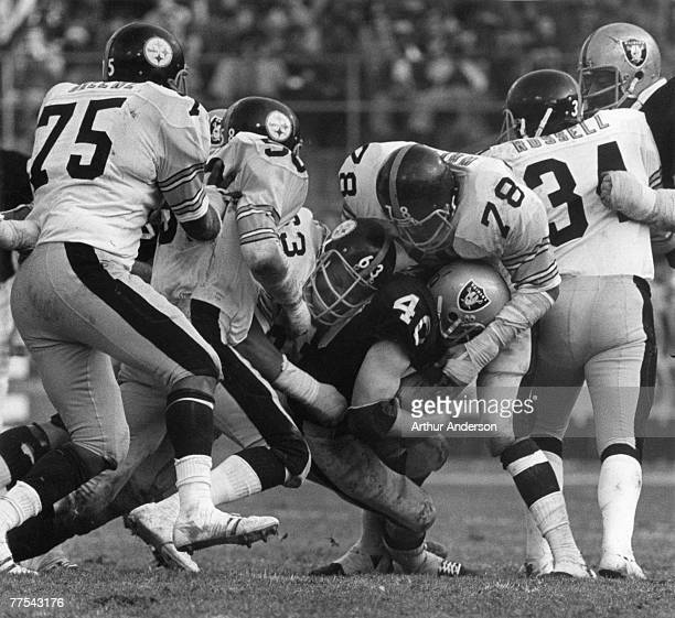 Oakland fullback Pete Banaszak is engulfed by Pittsburgh defensive end Dwight White linebacker Jack Lambert defensive tackle Ernie Holmes and Mean...