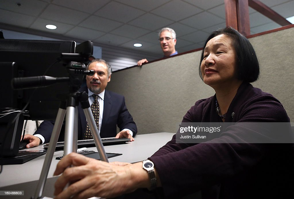 Oakland mayor Jean Quan (R) adjusts a camera to take her photo as she registers for the new Oakland Municipal identification card on February 1, 2013 in Oakland, California. Oakland became the first city in the nation to offer a municipal identification card that also doubles as a debit card. The card is available to all city residents as well as illegal immigrants and will allow people to use the debit card function to avoid check-cashing fees. The city expects to issue at least 6,000 of the $15 cards in the first year.