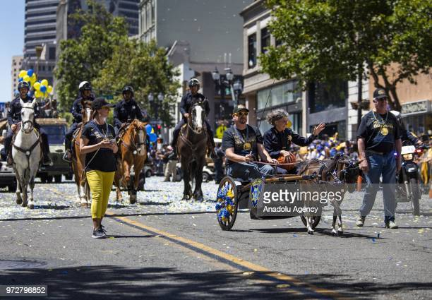 Oakland Police Chief Anne Kirkpatrick rides along the parade route in a carriage pulled by a pony during the Golden State Warriors NBA Championship...