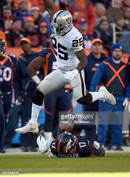 Oakland Raiders cornerback D.J. Hayden leaps over Denver Broncos quarterback Brock Osweiler after a slide and short gain during the first quarter...