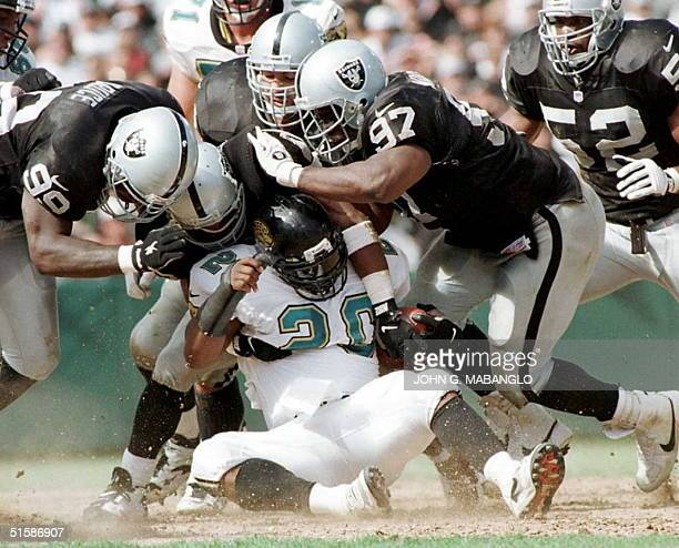 Oakland Raiders defensive end Aundray Bruce and defensive tackle Russell Maryland knock running back Natrone Means of the Jacksonville Jaguars to the...