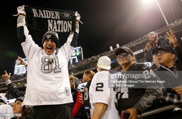 Oakland Raiders fan Carlos Trevino of Boulder Creek celebrates a fourth quarter touchdown against the Denver Broncos at the Coliseum in Oakland Calif...