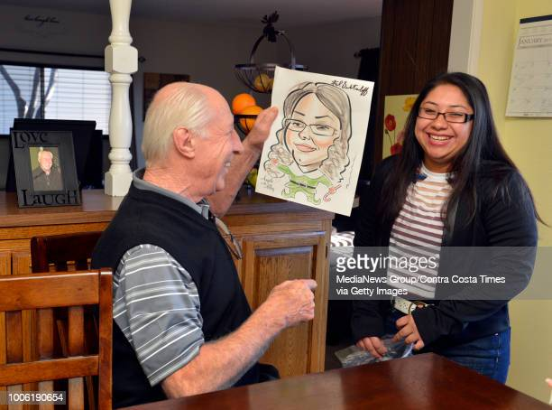 Oakland Raiders football legend Fred Biletnikoff holds up a caricature of Melissa Mendoza who can't help but smile during the exchange where...
