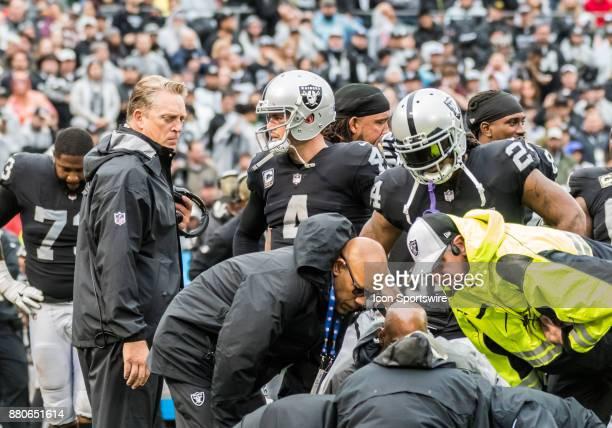 Oakland Raiders head coach Jack Del Rio talks with Oakland Raiders quarterback Derek Carr while medics attend to Oakland Raiders wide receiver Amari...