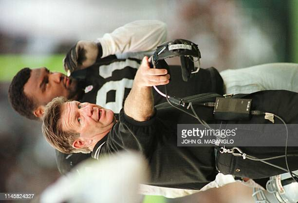 Oakland Raiders head coach Joe Bugel questions a penalty called against the Raiders as defensive end Chester McGlockton listens 08 September during...