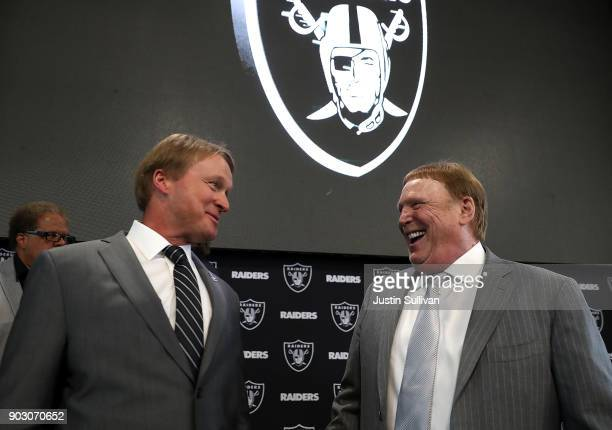 Oakland Raiders new head coach Jon Gruden talks with Raiders owner Mark Davis during a news conference at Oakland Raiders headquarters on January 9...