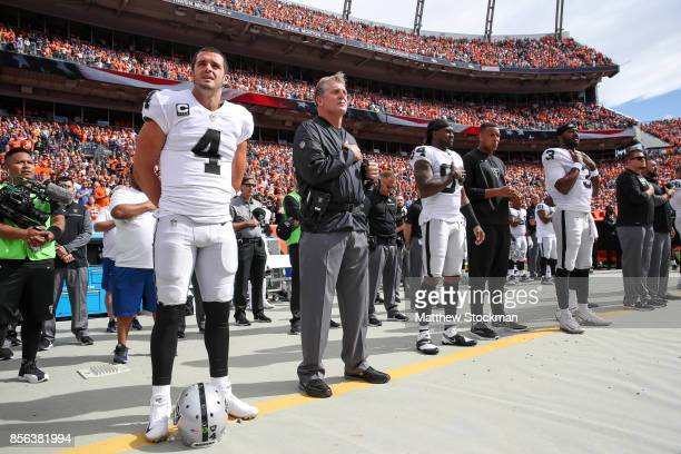 Oakland Raiders personnel including Derek Carr and head coach Jack Del Rio stand during the national anthem before a game against the Denver Broncos...