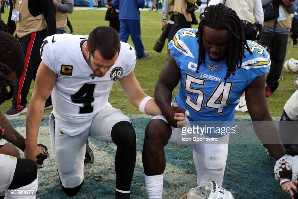 Oakland Raiders Quarterback Derek Carr and Los Angeles Chargers Defensive End Melvin Ingram III pray together after an NFL game between the Oakland...