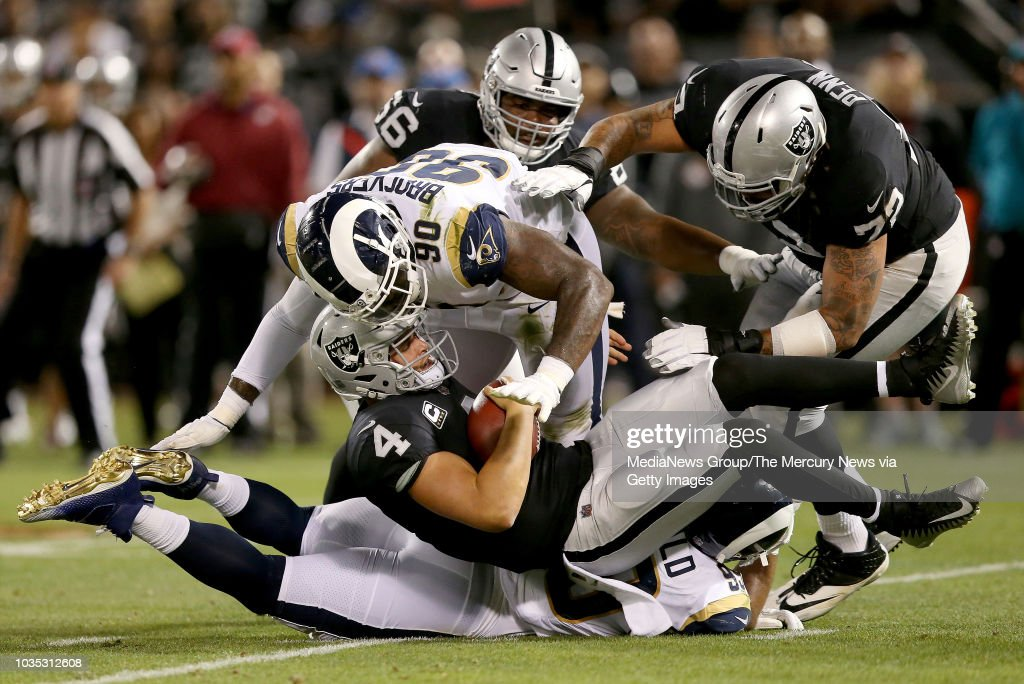 Oakland Raiders quarterback Derek Carr #4 is sacked by Los Angeles Rams defensive tackle Michael Brockers #90 and a defensive penalty is called in the first quarter of their NFL game at the Coliseum on September 10, 2018 in Oakland, California.