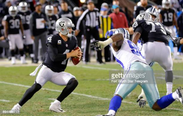 Oakland Raiders quarterback Derek Carr passes under pressure from Dallas Cowboys defensive end Demarcus Lawrence on Sunday Dec 17 2017 at...
