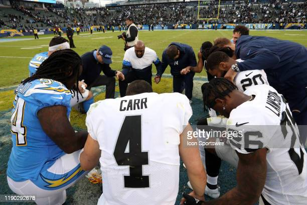 Oakland Raiders Quarterback Derek Carr prays with other players after an NFL game between the Oakland Raiders and the Los Angeles Chargers on...