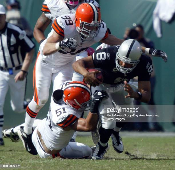 Oakland Raiders quarterback Jason Campbell is tackled by Cleveland Browns Scott Fujita and Chris Gocong in the second quarter of their NFL game at...