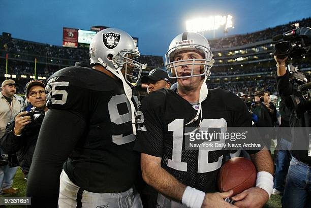 Oakland Raiders' quarterback Rich Gannon walks off the field with the game ball accompanied by defensive tackle Sam Adams after beating the New York...