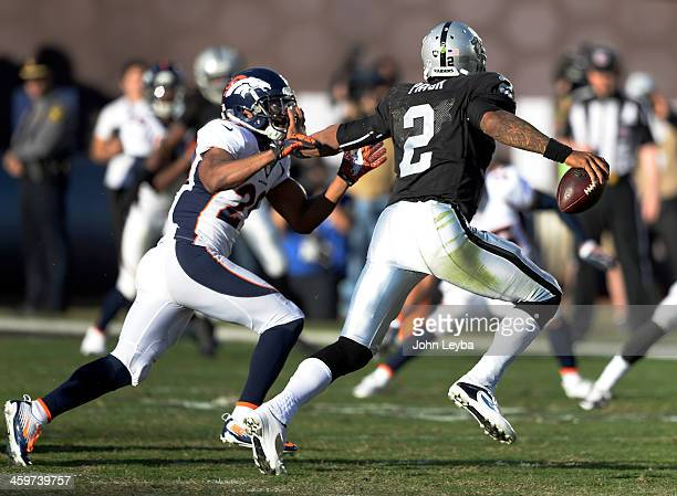 Oakland Raiders quarterback Terrelle Pryor stiff arms Denver Broncos free safety Michael Huff as he scrambles out of the pocket during the third...