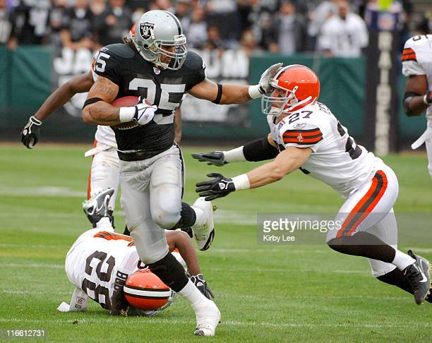 Oakland Raiders running back Justin Fargas straight arms Cleveland Browns defensive back Brian Russell on a 48yard run in the second quarter at...